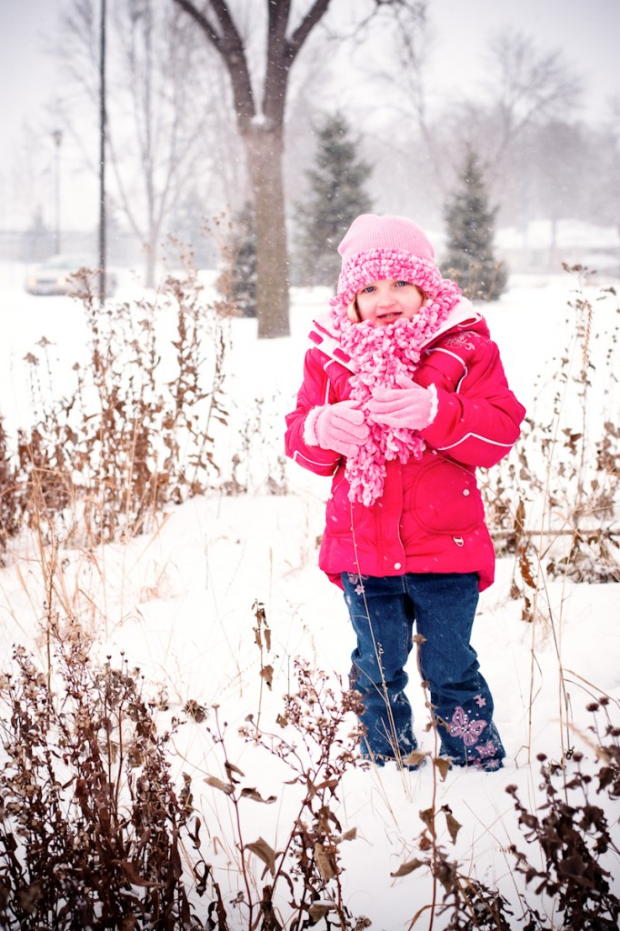 girl outside in snow with pink hat scarf and jacket
