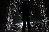 Night silhouette of girl on swing with spraying snow and ice